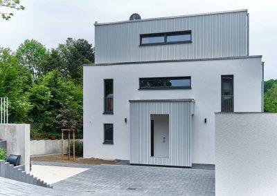 Straßenansicht Zweifamilienhaus mit schmalen Schlitzfenstern in Bensberg.