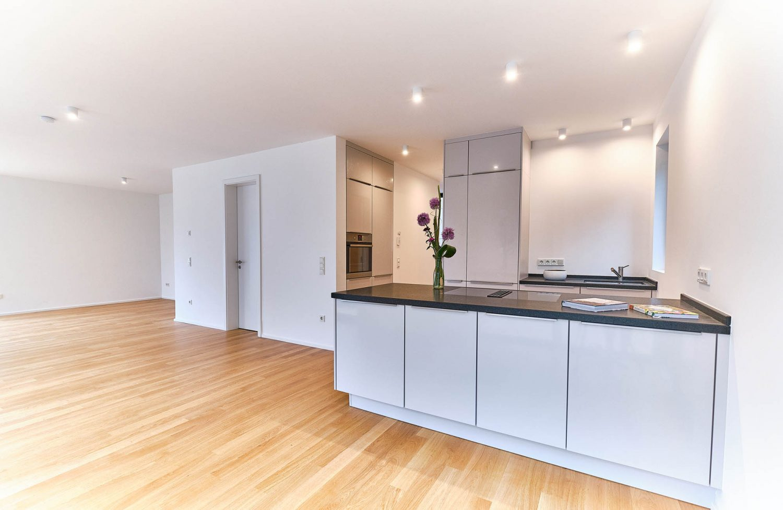 Hell gehaltene, offene Küche und großzügiger Wohnbereich im Neubau in Bensberg.