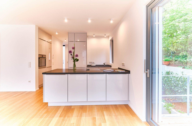 Offene Küche mit Zugang zum Außenbereich im Neubau in Bensberg.