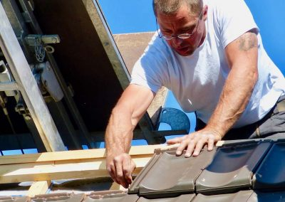 Dachdecker verlegt Dachziegel