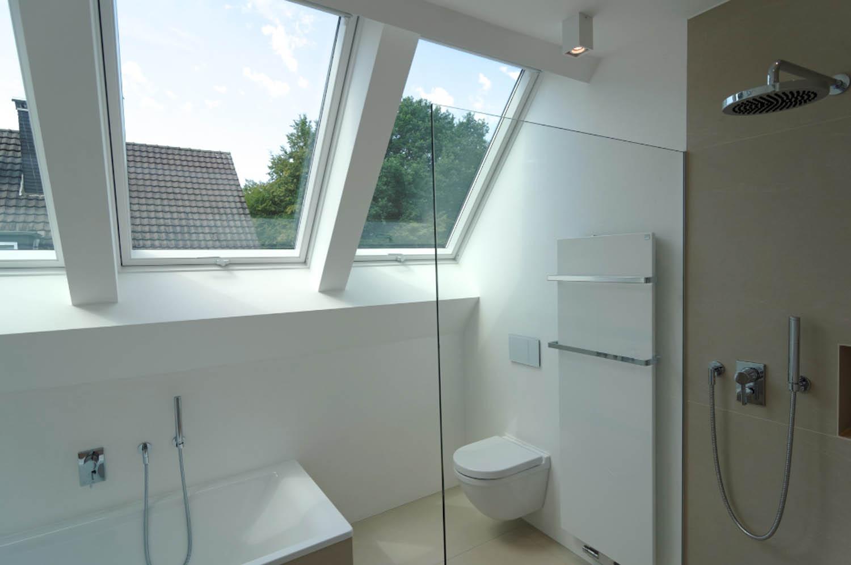 Helles Badezimmer mit WC, Badewanne, Dusche und drei Fenstern in der Dachschräge.