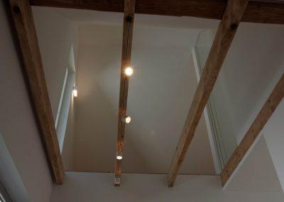 Aufgearbeitete Holzbalken mit Beleuchtung im ausgebauten Dachboden.
