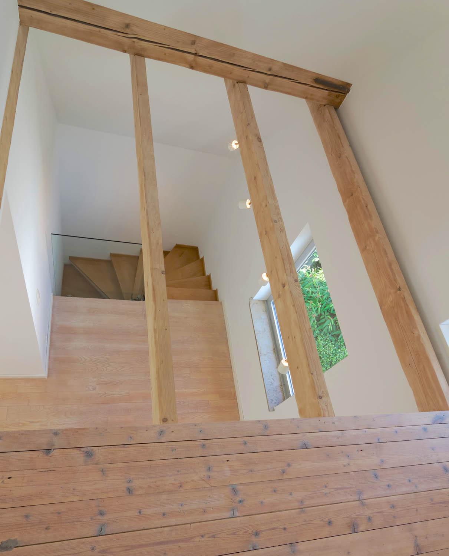 Blick vom Spitzboden auf Treppenhaus mit aufgearbeiteter Holztreppe.