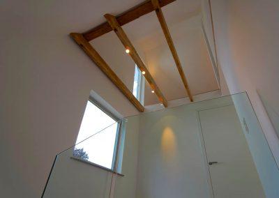 Aufgearbeitete Deckenbalken und Ganzglasgeländer im Treppenhaus zum ausgebauten Dachgeschoss.