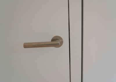 Türklinke an weißer Zimmertür.