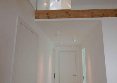 Aufgearbeitete Holzbalken und Lichtkonzept im Flur des Dachgeschoss.