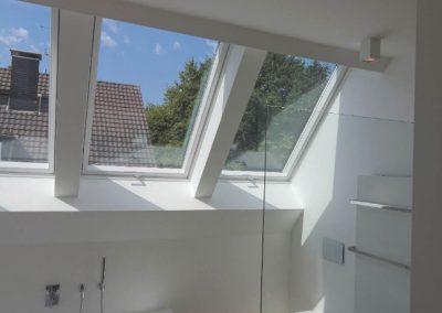 Helles Badezimmer mit WC und Badewanne und drei Fenstern in der Dachschräge.