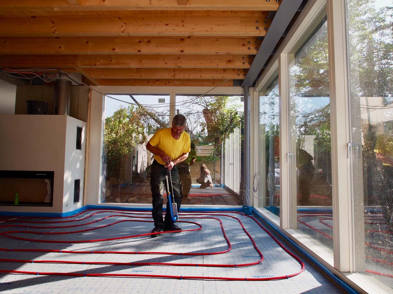 Installateur verlegt Fußbodenheizung