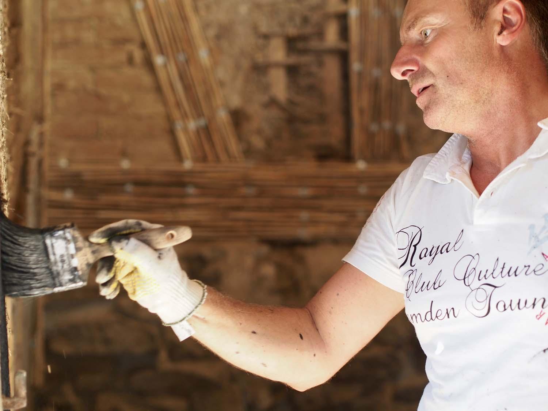 Malermeister streicht im Fachwerkhaus