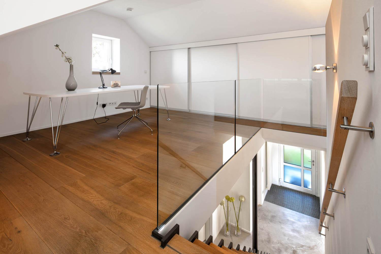 Der Arbeitsplatz im Obergeschoss ist zum Treppenaufgang mit einem Ganzglasgeländer abgetrennt.