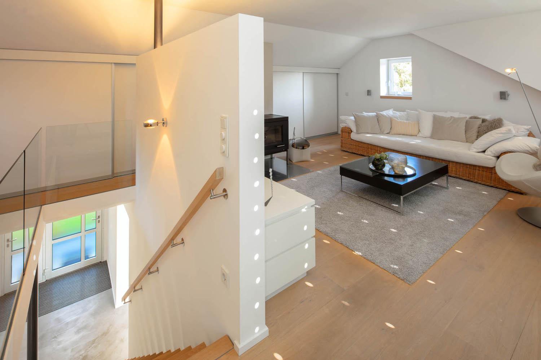 Wohnbereich mit breitem Rattansofa und weißer Möblierung.
