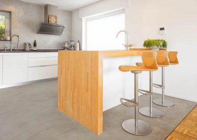 Arbeitsfläche und Sitzmöglichkeit in der Küche, die in den Raum hineinragt.