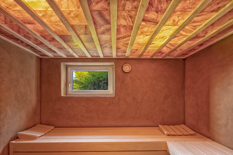 Sauna mit hinterleuchteter Salzsteindecke und Lehmwänden.