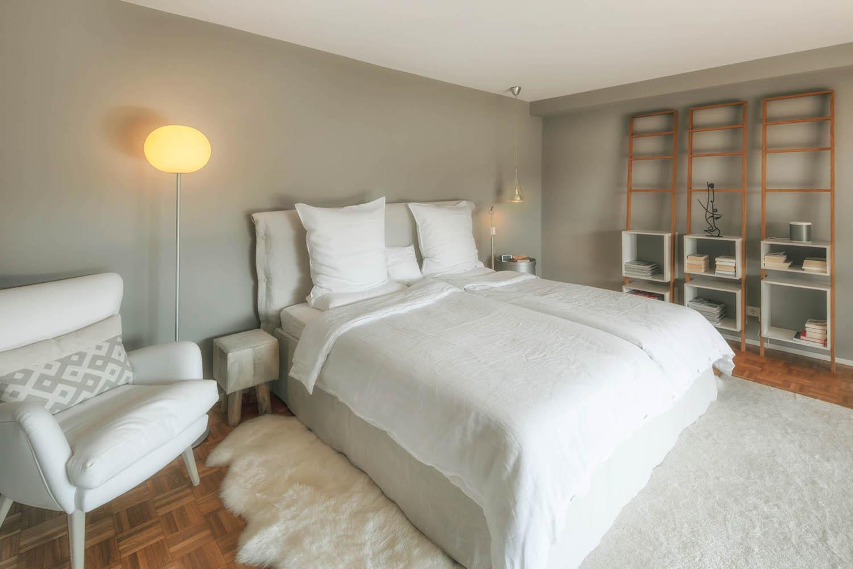 Schlafzimmer mit grauen Wänden und Parkettboden nach der Modernisierung.