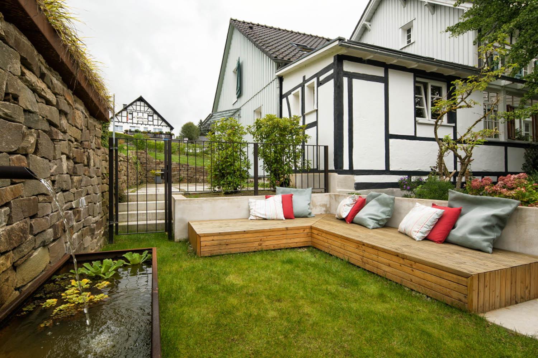 Begrünter Innenhof mit Natursteinmauer, Brunnen und Sitzmöglichkeit vor einer sanierten Fachwerk-Fassade.