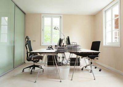 Arbeitszimmer mit zwei gegenüberstehenden Schreibtischen.