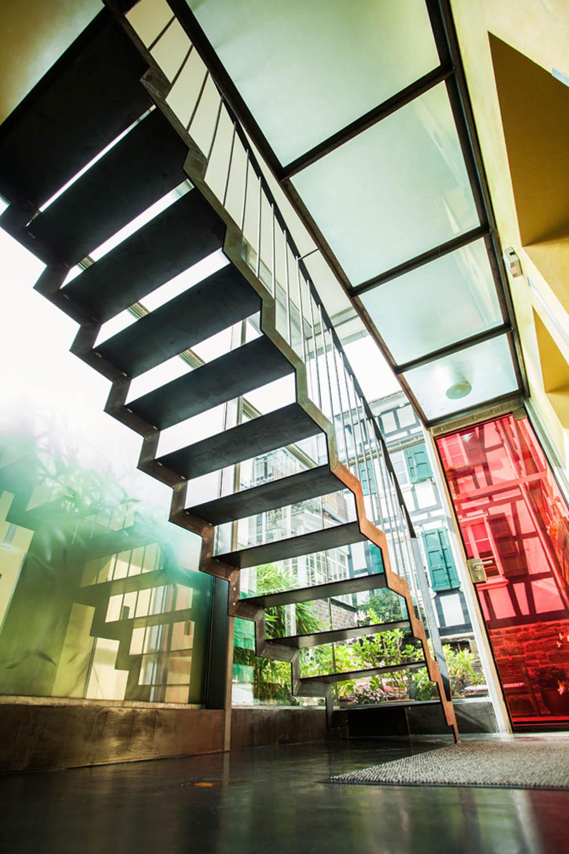 Rote Glastür im verglasten Treppenhaus mit Blick unter die Stahltreppe.