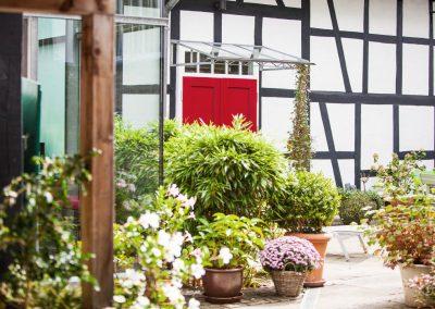 Innenhof mit vielen bepflanzten Blumenkübeln vor sanierten Fachwerkwänden.