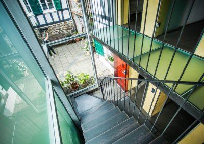 Verglastes Treppenhaus mit Stahltreppe ins Untergeschoss und Blick in den Innenhof..