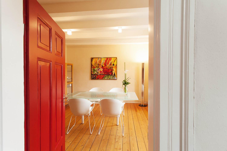 Trauzimmer mit Holzdielen Glastisch und roter Zimmertür.