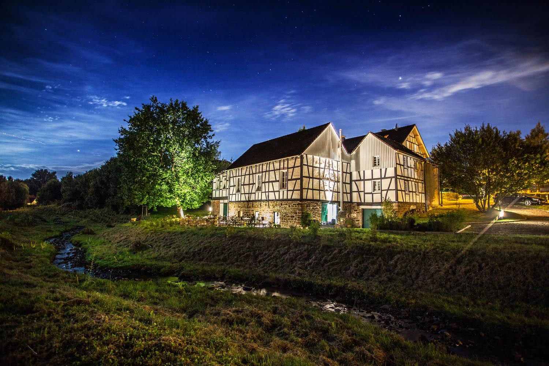Saniertes Fachwerkhaus und dahinter liegender Bach kontrastreich bei Nacht fotografiert.