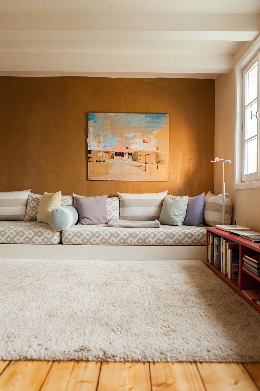 Wohnbereich mit Hochflorteppich auf Hozdielenboden und auffälliger Lehmwand.