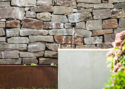 Brunnen an Natursteinmauer.
