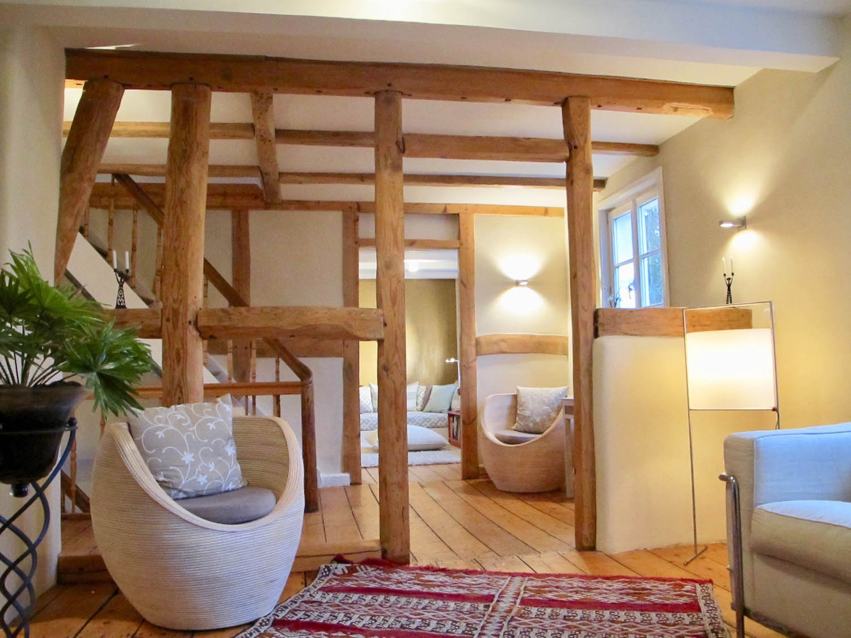 Wohnbereich mit sichtbaren und aufgearbeiteten Holzbalken des Fachwerkbaus.
