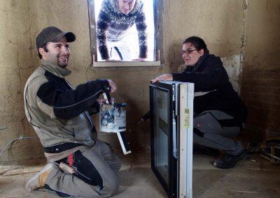 Schreinermeister montiert Fenster in Rahmen