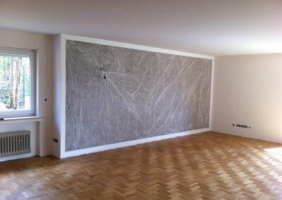 Die in grau gestaltete Innenwand zeigt durch eine besondere Gestaltungstechnik einen Marmoreffekt.