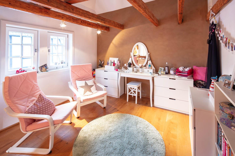 Ankleidezimmer mit Lehmwand und freiliegenden Holzbalken